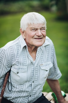 Stock photo portrait of a old caucasian man in checked shirt with two chest pockets with a crutch beneath an armpit sittingon a bench outdoors and smiling at camera.