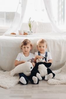Foto di stock ritratto di due adorabili bambini seduti sul pavimento con due giocattoli di peluche in mani