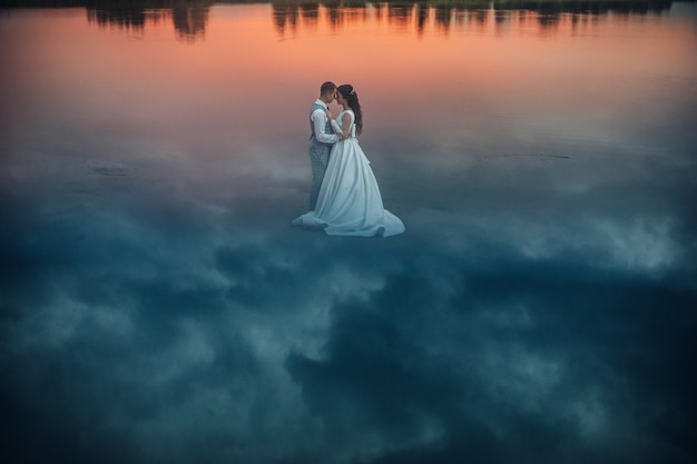 Stock photo of a romantic bride in wedding dress and groom in suit hugging face to face standing on wet sand with sky reflection on it. clouds reflecting on the ground making a fantastic view.