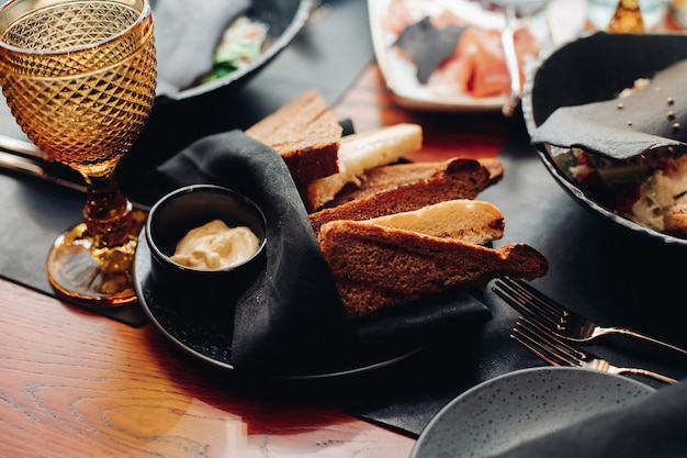 Stock photo of slices of white and brown bread on black napkin with a sauce in black saucer on black plate on served table in restaurant.