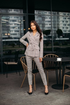Stock photo of a trendy model in checked beige suit and black heels with long wavy brown hair posing next to black table and chair outside restaurant or cafe
