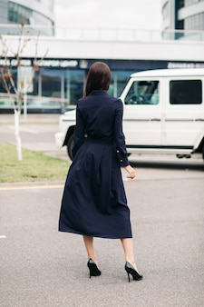 Foto di stock di una donna bruna irriconoscibile in abito nero cottong con gonna lunga e tacchi in pelle nera in piedi in strada.