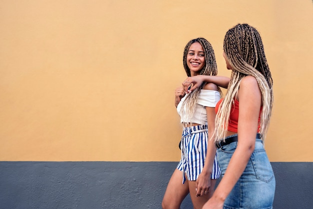 Stock photo of young african american sisters walking in the street.