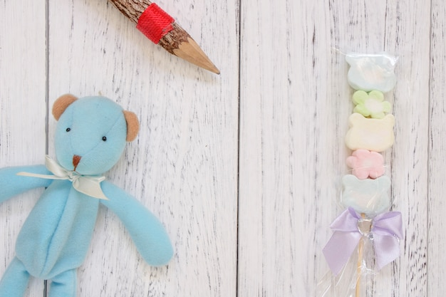 Stock photography flat lay vintage white painted wood table blue bear doll cotton candy pencil