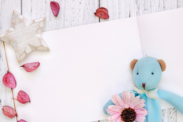 Stock photography flat lay vintage white painted wood table purple flower petals bear doll star craft