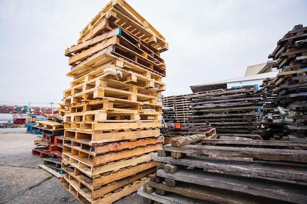 해체하고 재활용할 준비가 된 마당에 있는 나무 팔레트 더미.