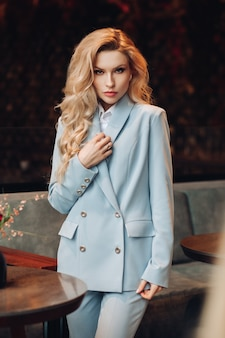 Stock portrait of a stunning elegant woman with long wavy blonde hair wearing light blue business suit with trousers. she is looking at camera precisely. business lady in suit in cafe.