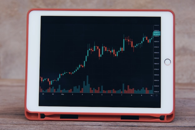 Stock trading forex on tablet on a wooden table