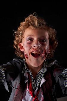 Стандартное вертикальное фото мальчика, замаскированного под зомби, с выражением веселья. хэллоуин