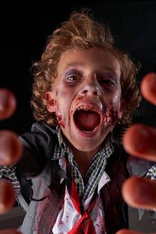 Стоковое вертикальное фото лица мальчика, замаскированного под зомби с кровью и блеском, с руками перед собой и кричащим