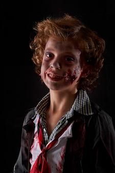 Стандартное вертикальное фото ребенка, замаскированного под зомби с кровью и блеском. хэллоуин