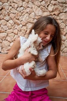 그녀의 얼굴을 핥고 그녀의 팔에 그녀를 안고 작은 흰색 강아지와 찡그린 여자의 스톡 세로 사진. 애완 동물과 가족