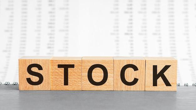 Слово запаса написано на деревянном блоке на фоне столбцов чисел. фондовый текст на деревянном столе для вашего дизайна, концепции