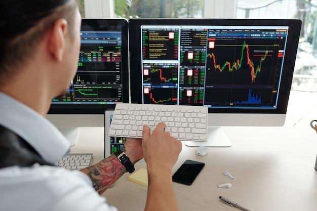 Биржевой маклер покупает и продает акции от имени клиентов, он смотрит на экран компьютера и нажимает кнопку на клавиатуре.