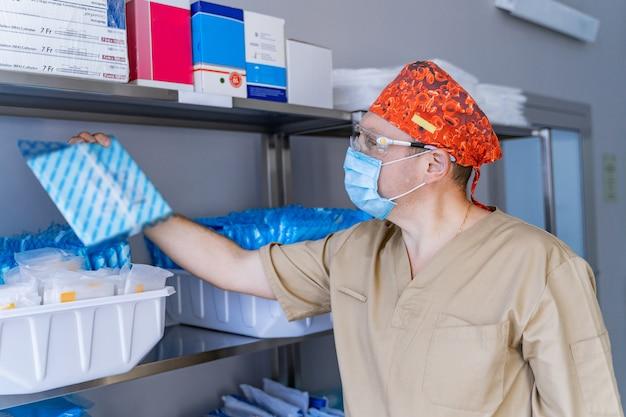 Stocked shelves of medical scrubs in storeroom. assistant gets stuff. scrubs, medical masks, antiseptic, health care and prevention methods. sanitizer.