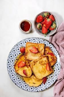 Запас французских тостов со свежей клубникой на керамической тарелке, кленовым сиропом в керамическом кувшине и салфеткой из розовой ткани на белой поверхности. вид сверху, плоская планировка. копировать пространство