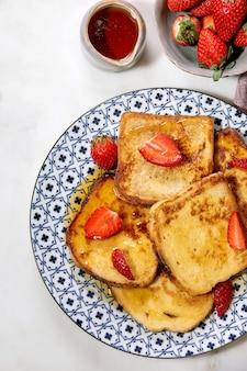 Запас французских тостов со свежей клубникой на керамической тарелке, кленовый сироп в керамическом кувшине над белой мраморной поверхностью. вид сверху, плоская планировка, космос