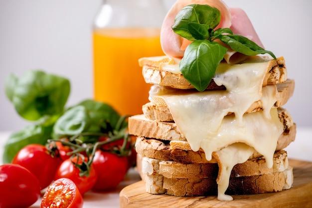 구운 녹은 치즈의 비축 햄 고기, 체리 토마토, 오렌지 주스 및 바질과 함께 샌드위치를 누르면 나무 커팅 보드에 나뭇잎. 확대