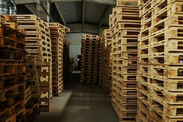Запасы деревянных поддонов для доставки больших партий товаров.
