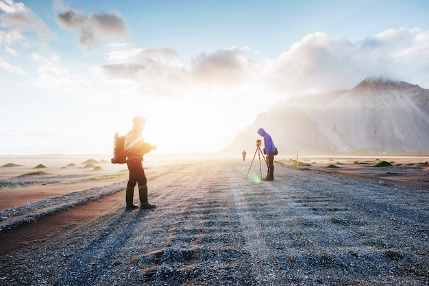 Фантастический запад гор и вулканических лавовых песчаных дюн до пляжа stokksness. туристы, путешествующие по пустыне