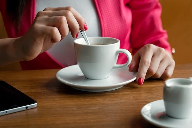 クローズアップ、若い女の子の手は、コーヒーのカップに砂糖をかき混ぜ、木製stolikosの後ろのカフェに座っています。