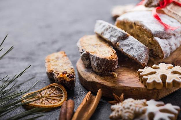 Stollen. sliced homemade christmas dessert stollen with dried berries and nuts on stone  rustic table with cinnamon, orange slices, christmas tree branches, gingerbread , selective focus