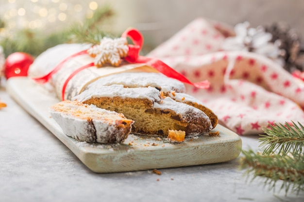 Stollen a traditional european cake with nuts and candied fruit, is dusted with icing sugar and cut into pieces