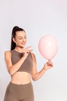 복통 개념-복부 팽창, 경련, 통증 완화. 핑크 풍선 옆에 바늘을 들고 젊은 여자.