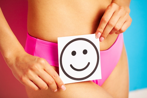 Stomach health and good digestion concepts, close up of healthy woman with beautiful fit slim body in pink panties holding card with happy smile in hands.