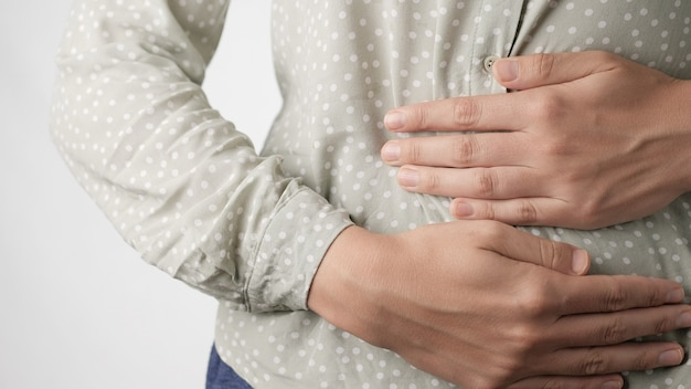 Stomach pain female hands restlessly touching belly on white background closeup