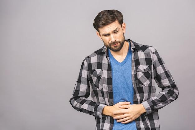 胃の痛みや食事の問題。気分が悪く、カジュアルな立ち姿で痛みを伴う腹を抱えて病気のハンサムな若いひげを生やした男の肖像。灰色の灰色の壁の壁に分離されました。