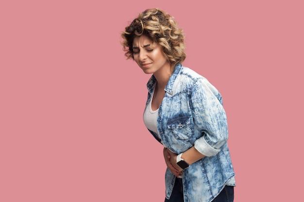 복통. 파란 셔츠에 곱슬머리를 하고 서서 고통스러운 배를 잡고 있는 화난 젊은 여성의 프로필 측면 초상화. 실내 스튜디오 촬영, 분홍색 배경에 격리.