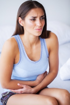 Stomach pain. unhealthy young woman with stomachache leaning on the bed at home