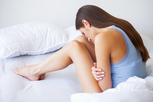 Stomach pain, unhealthy young woman with stomachache leaning on the bed at home