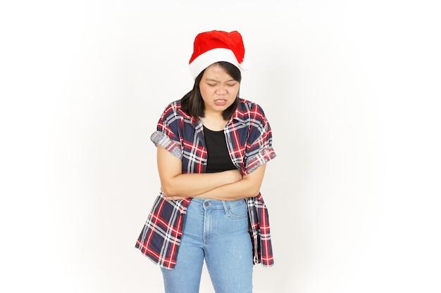 Боль в животе красивой азиатской женщины в красной клетчатой рубашке и шляпе санты, изолированной на белом