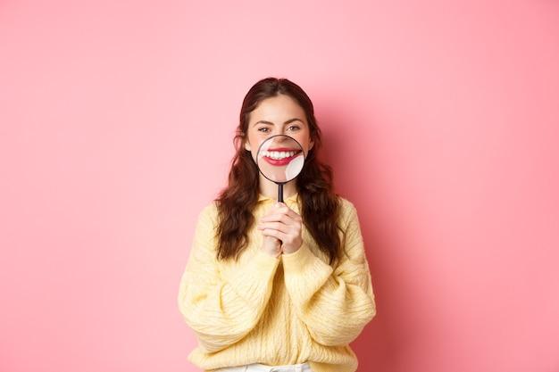 구강 및 의료 개념입니다. 분홍색 배경에 서서 돋보기로 하얀 치아를 보여주는 완벽한 미소를 가진 젊은 아름다운 소녀.