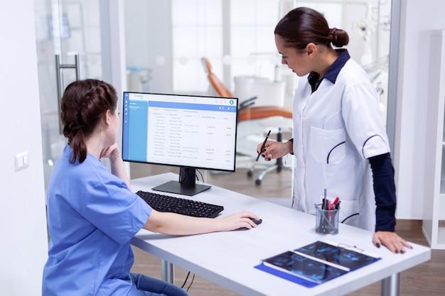 Стоматолог и медсестра в зубной клинике проверяют назначение пациента, глядя на монитор компьютера. помощник стоматолога и зубной врач обсуждают в приемной стоматологического кабинета
