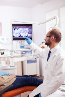Стоматолог объясняет стоматологическое лечение пожилой женщине во время осмотра, смотрящего на рентгеновский снимок. берущий уход за медицинскими зубами указывая на рентгенографию пациента на экране сидя на стуле.