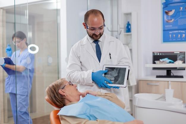 診断を説明する年配の女性の相談中の制服を着たstomatolog。立っている患者の近くのタブレットpcで患者のレントゲン写真を保持している医療の歯の世話人。