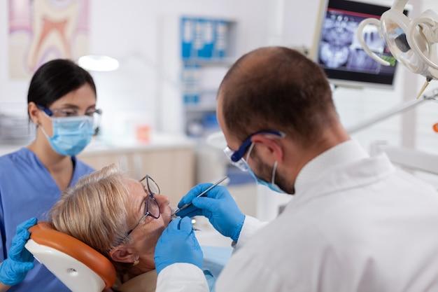 Stomatolog and nurse treats teeth of senior woman using drill
