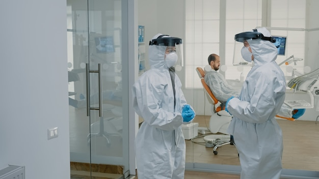 Stomatological doctors wearing ppe suits at dental clinic