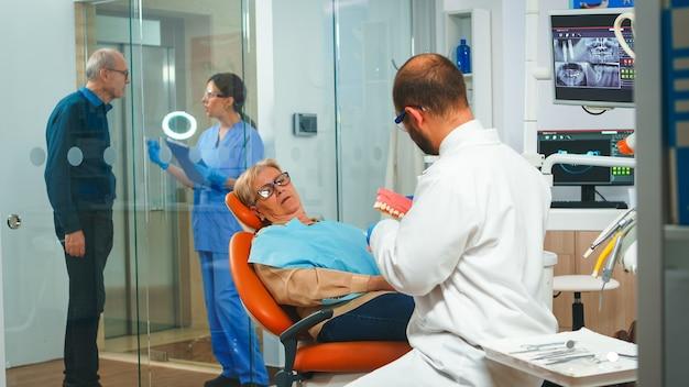 高齢患者と話す下顎の石膏モデルを保持している口腔病学者。歯の骨格のモックアップ、歯ブラシを使用した人間の顎のサンプルを使用して正しい歯科衛生を示す歯科医
