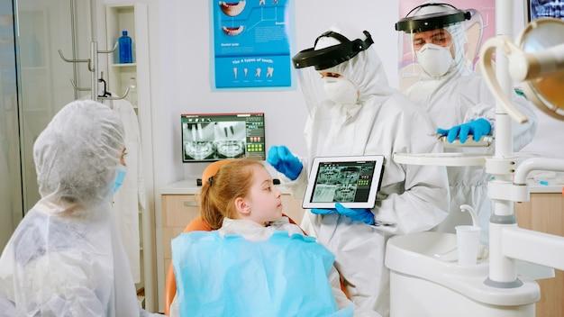 患者の母親と一緒にそれをレビューするタブレット歯科用x線で示す保護具の口腔病専門医。フェイスシールドマスク、手袋を着用し、ノートブックディスプレイを使用してx線撮影を説明する医療チーム