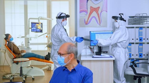 현대 클리닉에서 코로나바이러스 전염병 동안 치아 문제를 검사하는 환자 치과 엑스레이를 요청하는 보호복을 입은 구강 전문의. 작업복, 안면 보호대, 마스크, 장갑을 끼고 있는 의료 팀.