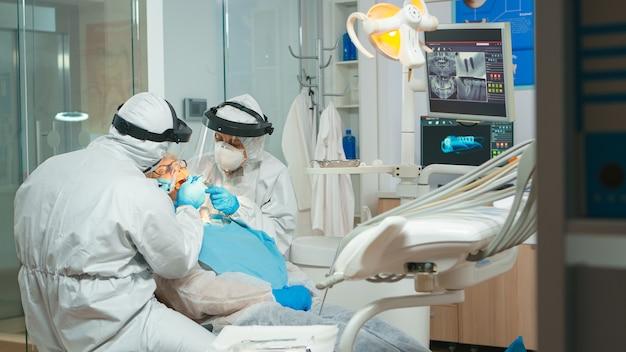 滅菌ツールを使用して歯の世話をする歯科検査を行う防護服を着た口腔病専門医。美容室でつなぎ服、フェイスシールド、マスク、手袋を着用して作業する医療チーム
