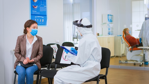 Covid-19パンデミックでクリップボードに書かれた治療法を説明する患者と一緒に登録フォームをレビューする防護服を着た口腔病学者。フェイスシールド、つなぎ服、マスク、手袋を着用した医療看護師。