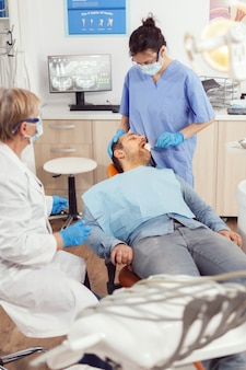 Stomatologist nurse looking in patient mouth preparing for dental surgery. dentist asisstant with face mask examining sick man with dental bib before intervention sitting on stomatological chair