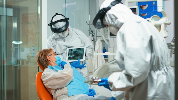Stomatologo in tuta protettiva che esamina i raggi x del dente con il paziente anziano che spiega il trattamento utilizzando il tablet nella pandemia di covisd-19. equipe medica che indossa visiera, tuta, maschera e guanti.