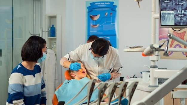 子供の母親と話し、ランプを点灯し、口腔病学の椅子の近くに立っている少女を調べる口腔病学者。看護師が滅菌ツールを準備している間、小児歯科医が女性に話しかけます。