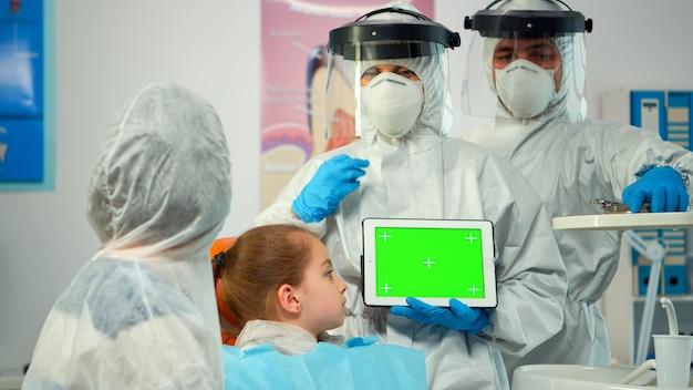 コロナウイルスの流行中にモックアップグリーンスクリーンディスプレイを指しているつなぎ服を着た口腔病学者。グリーンスクリーンモニター付きモニターの使用について説明するクロマキーizolatedクロマpcキーモックアップタッチスクリーン